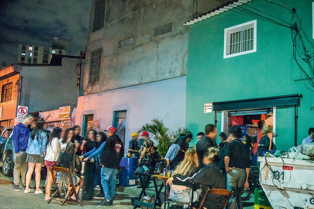 muitas pessoas bebendo e conversando em aglomeração de rua durante a pandemia na rua édson dias