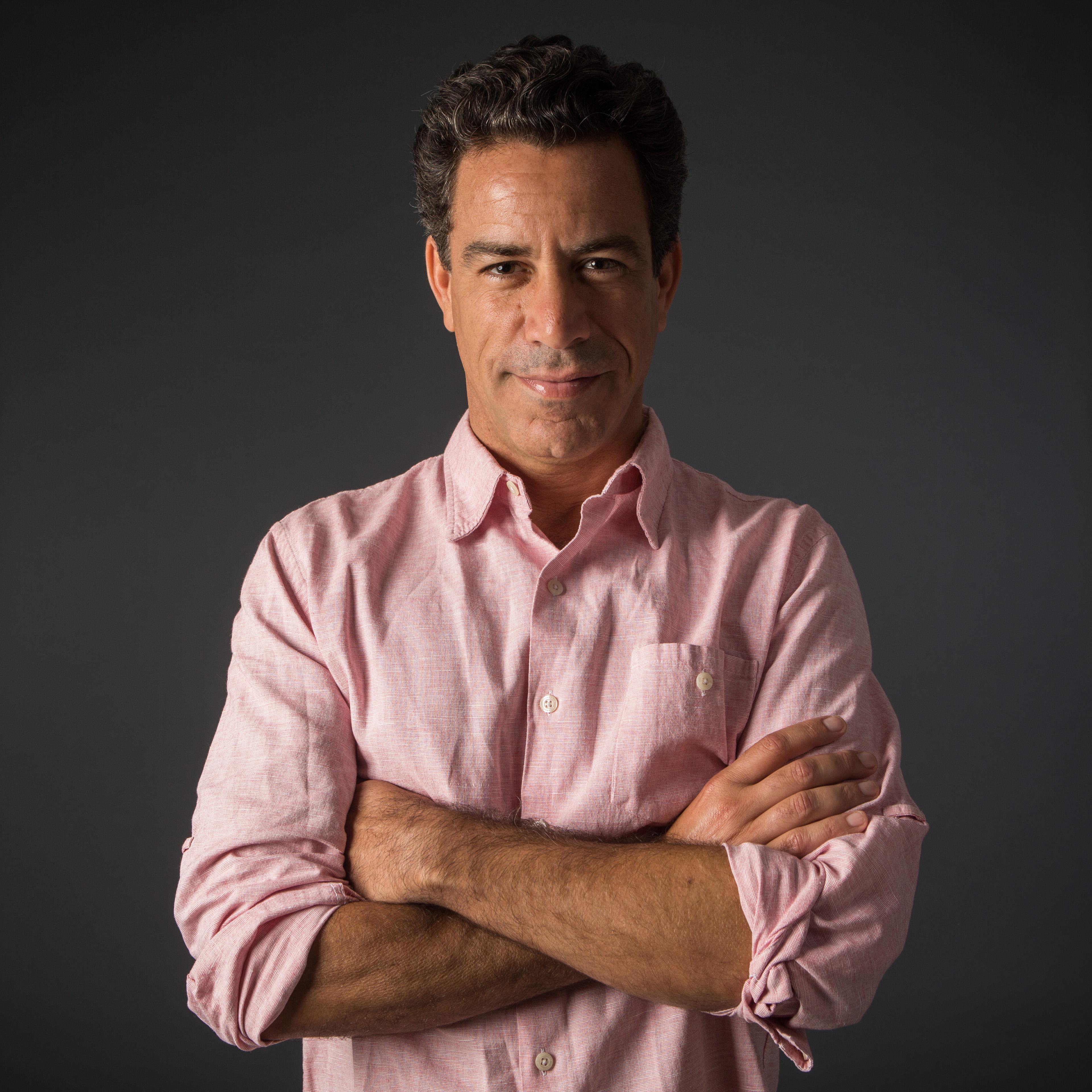 Luiz Calainho encara a câmera de braços cruzados. Fundo escuro ressalta sua camisa rosa de manga longa.