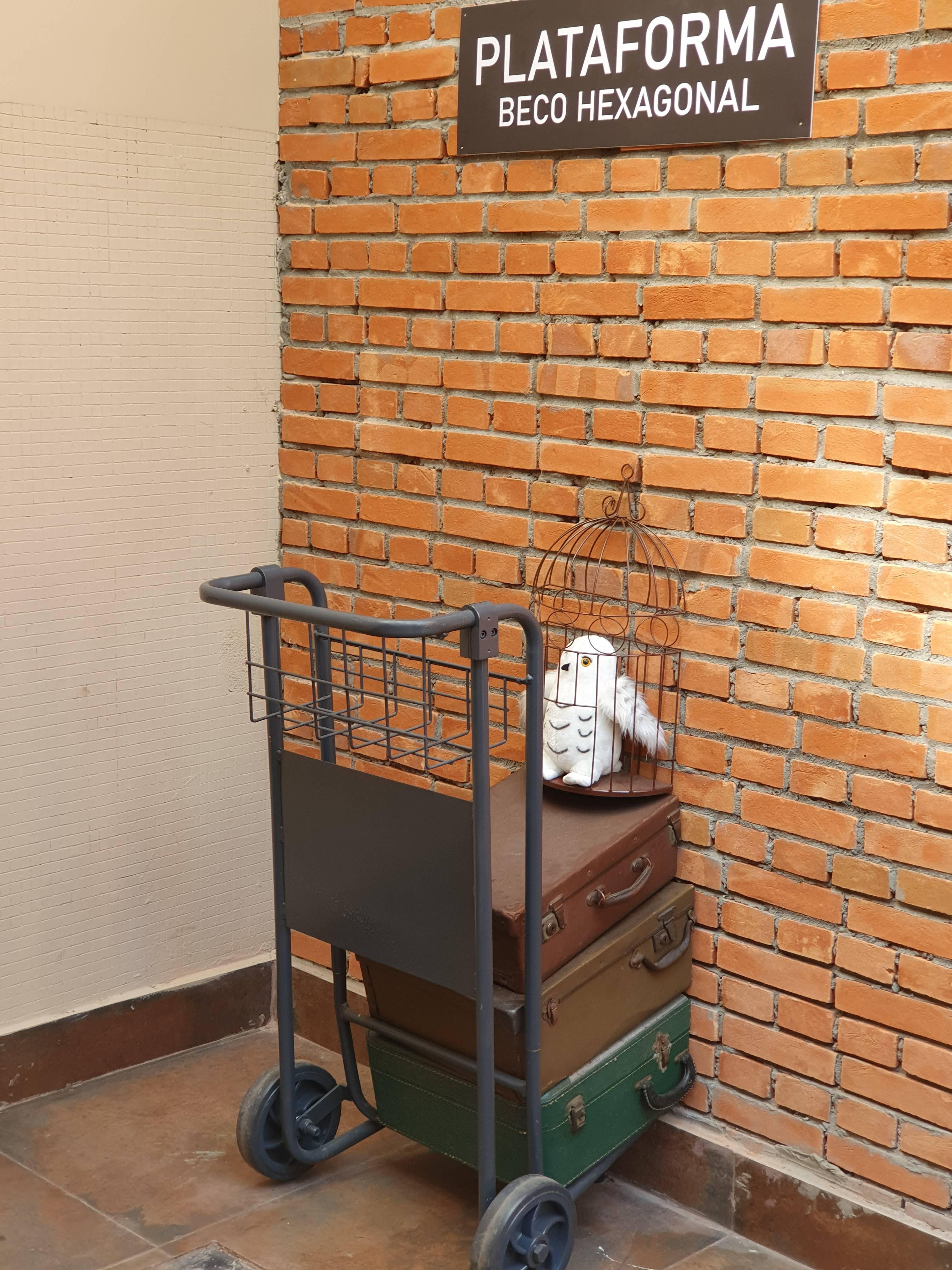 Carrinho de malas entrando em parede de tijolos; lê se em placa acima: