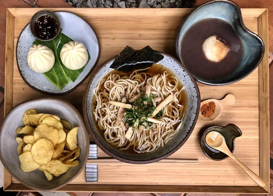 Foto aérea de mesa de madeira com potes de cerâmica com receitas preparadas pela chef Telma Shiraishi.