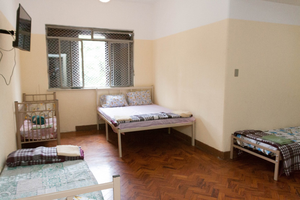 A imagem mostra um quarto no abrigo da prefeitura. É possível ver uma cama de casal, um janela, um berço e outra cama um pouco menor
