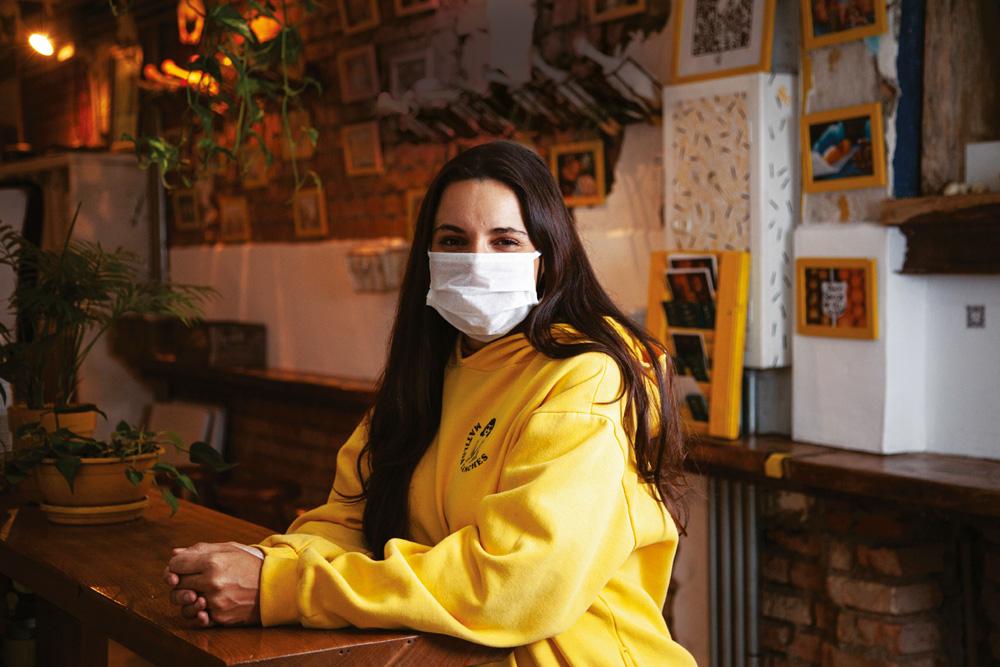 A chef Renata Vanzetto sentada, de moletom amarelo e máscara, com os braços apoiados sobre messa de madeira.