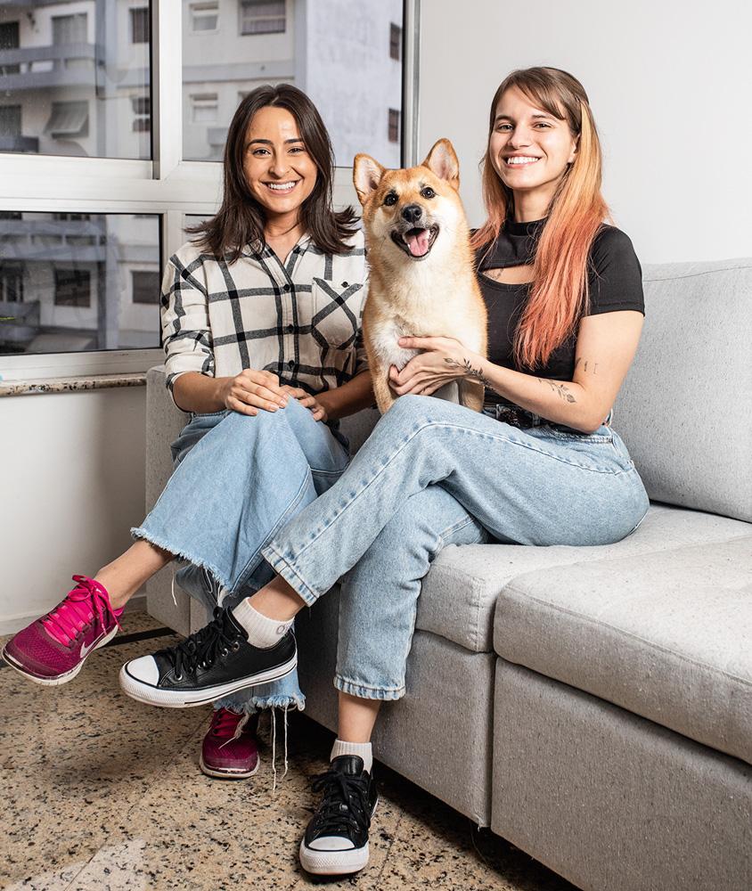 A imagem mostra as duas amigas sentadas em um sofá, com o cachorro no colo, sorrindo para a câmera.