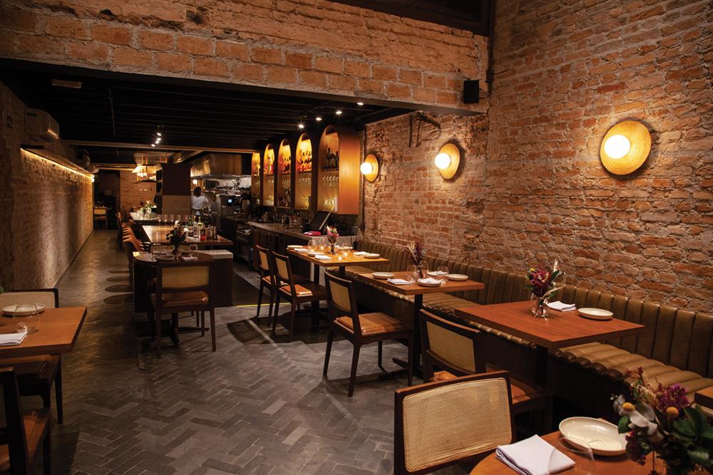 Salão do restaurante Nelita, com paredes de tijolo aparente e mesas alinhados do lado direito.