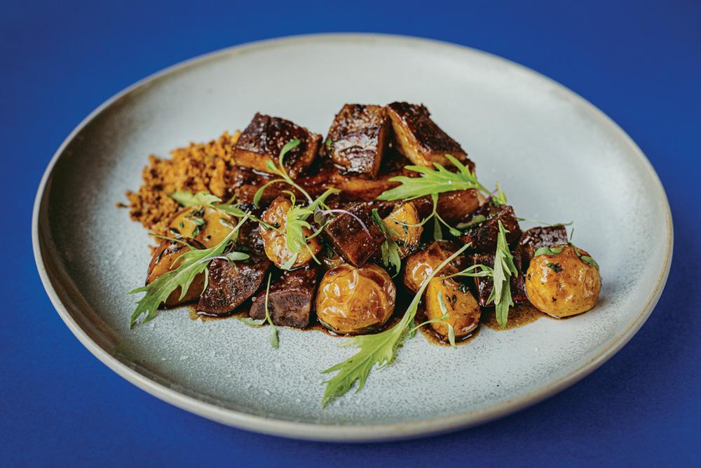 Prato de cerâmica sobre superfície azul com costelinha de porco picada junto de batatas assadas e à farofa.