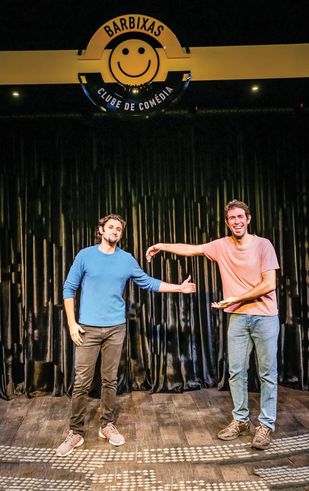 Dois homens fazem pose de abraço, mas com distanciamento social, em um palco de um clube de comédia. Eles estão sorrindo