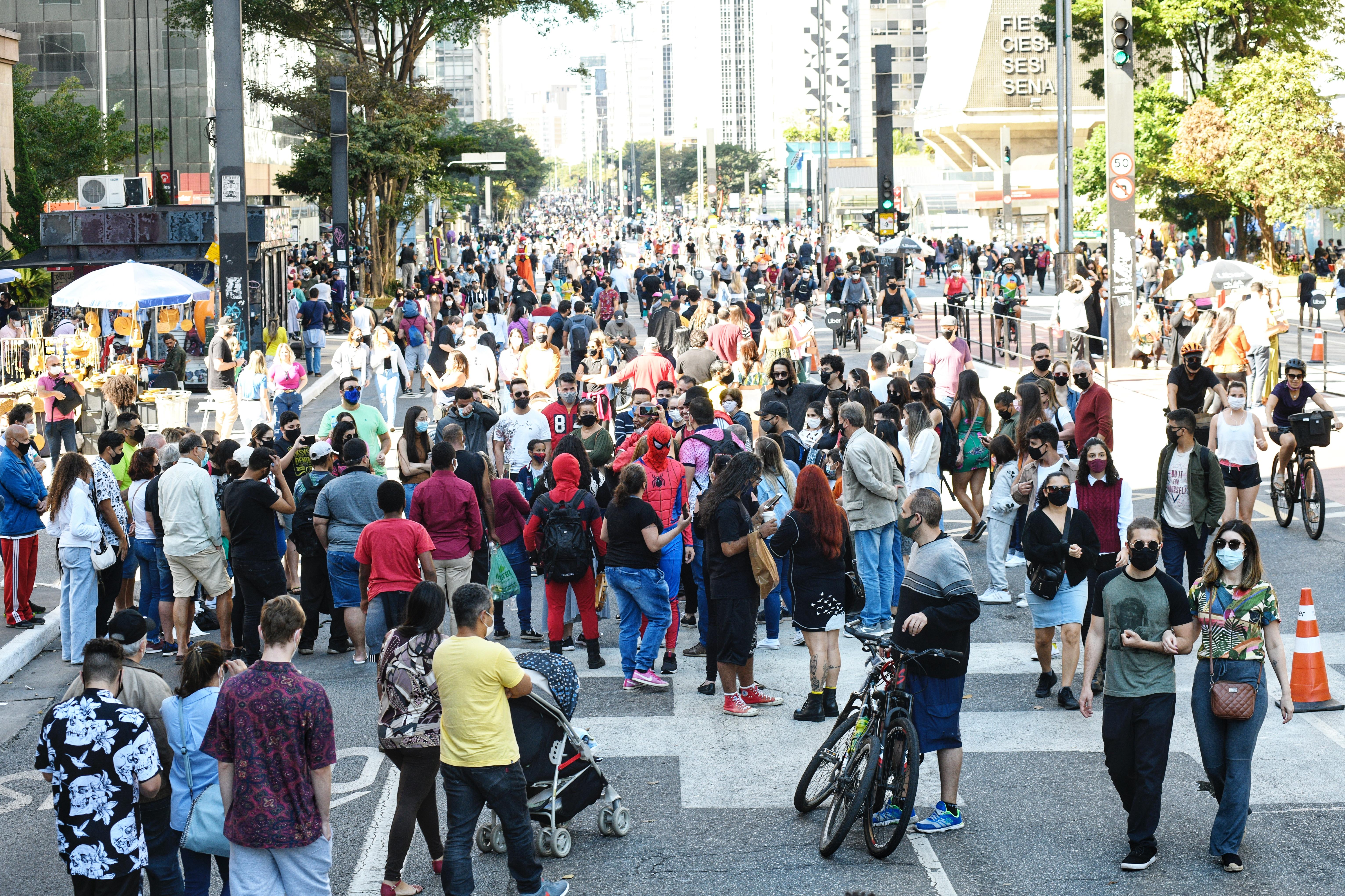 Imagem mostra grande quantidade de pessoas na Avenida Paulista neste domingo ensolarado de inverno. Muitas pessoas usam máscaras, mas muitas também não usam