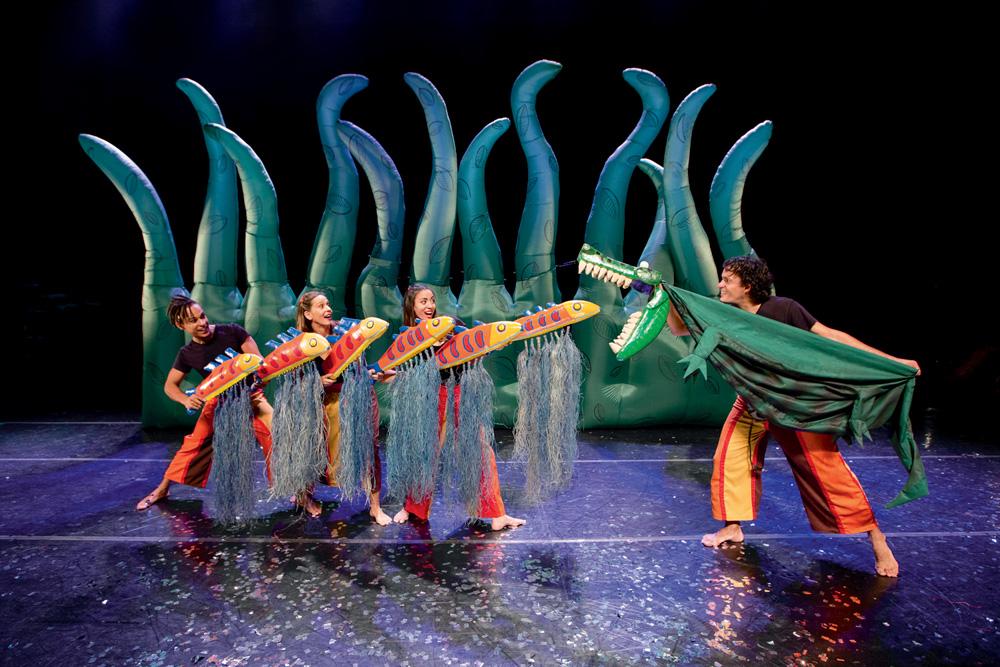 Três atores manuseiam bonecos de peixes e outro de um jacaré em um palco de teatro