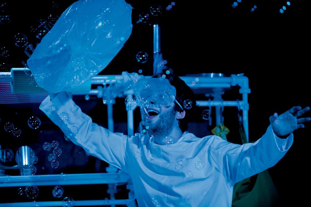 Homem em uma peça tem instrumento de proteção na cara enquanto olha animado para bolinhas de sabão. Imagem tem forte luz azul