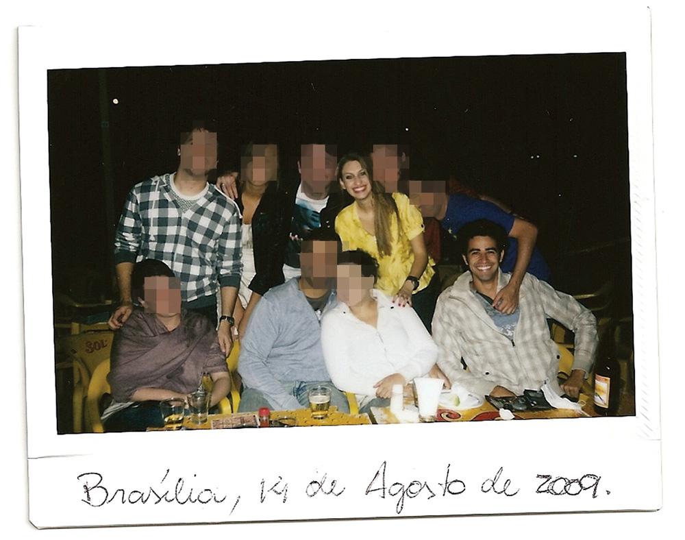 A imagem mostra Carol em pé e Tiago sentado em uma mesa de bar. Há várias outras pessoas em volta e os dois estão relativamente longe um do outro.