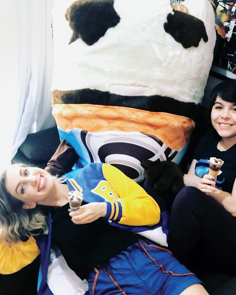 A imagem mostra Carol Moreira sentada em cima de uma pessoa fantasiada de corneto. Ela está com o sorvete na mão e sorrindo para o câmera.