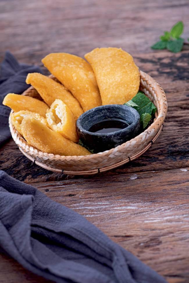 Cestinha de palha com mini pastéis amarelados junto de potinho com melaço sobre mesa de madeira.