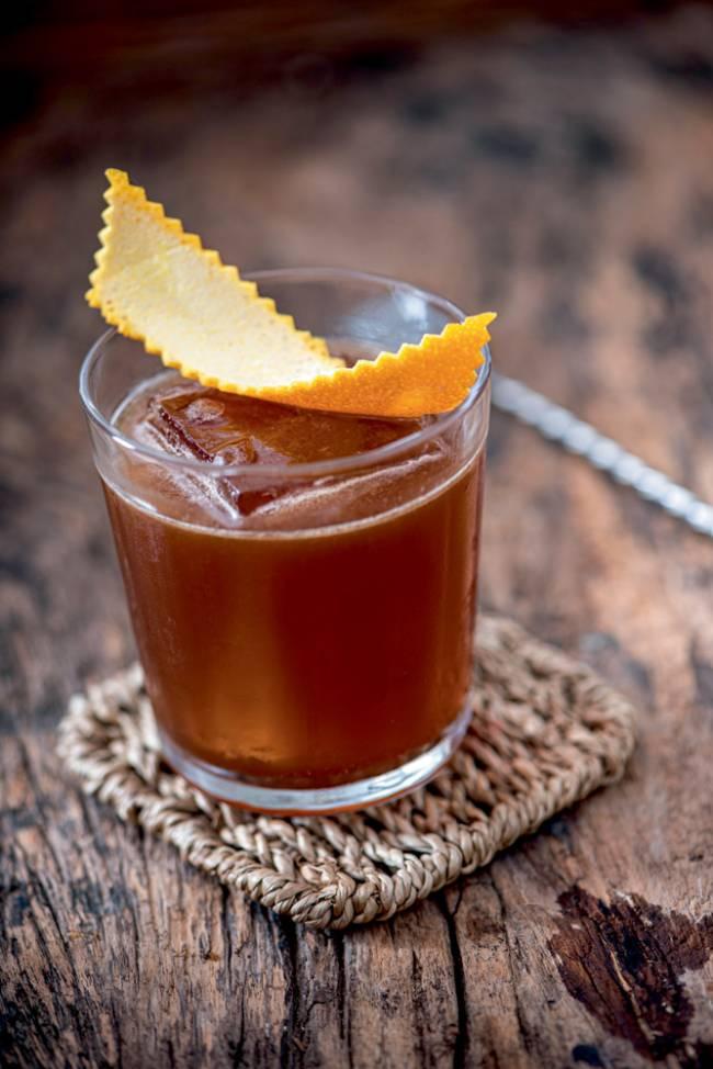 Drinque de cor caramelo com gelão quadrado coberto por casca de laranja sobre porta-copos em mesa de madeira.