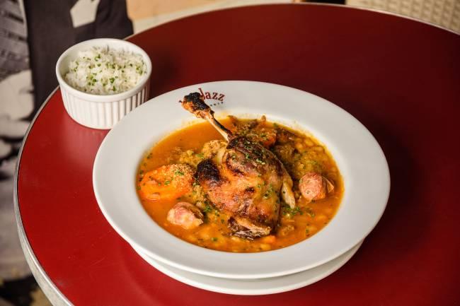 Cassoulet com coxa de frango assado sobre o cozido no prato fundo do Le Jazz sobre mesa vermelha ao lado de potinho de arroz.