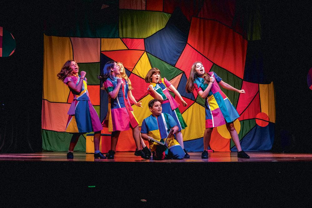 Seis crianças em cena, vestidas com a mesma roupa, de formas e coloridas, dançam em um palco de teatro