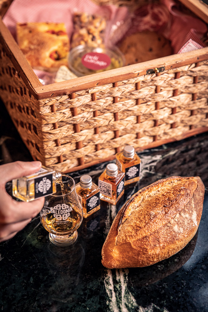 À frente, são visíveis doses de uísque em pequenas garrafas e um pão. Ao fundo, cesta de palha.