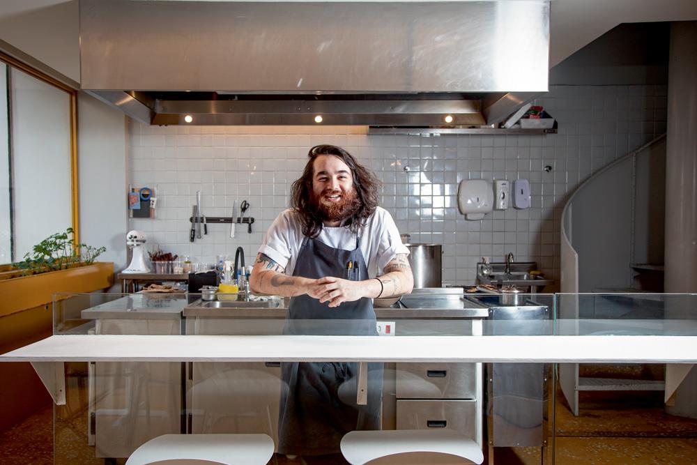 O chef, Raphael Vieira, usando uma camiseta branca e um avental de cor cinza por cima, posa na cozinha de seu restaurante.
