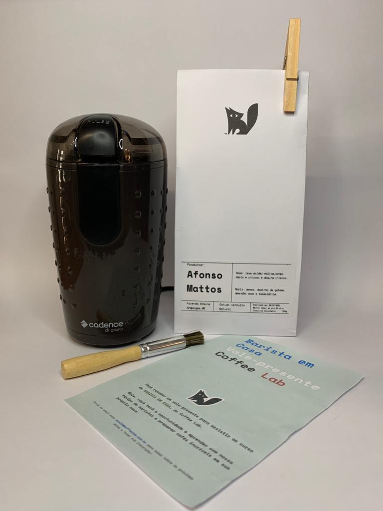 Kit com uma embalagem branca de café do lado direito, moedor de café e pincel e papel à frente.