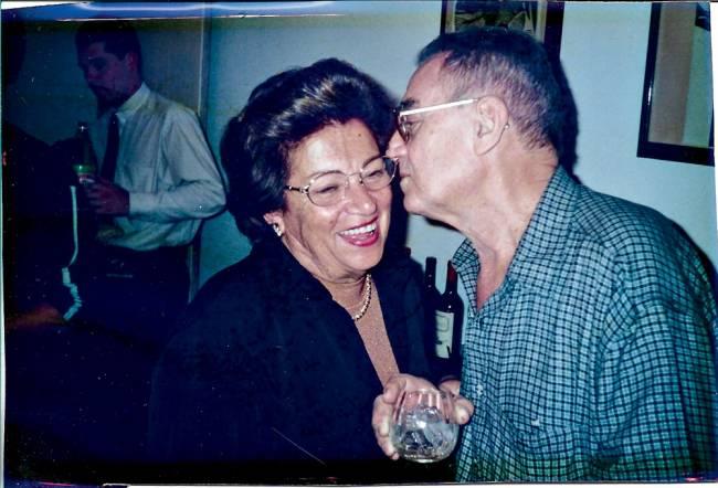 Foto azulada de Creusa e Décio Silva, fundadores do Hamburguinho, em festa, com ele à direita dando um beijo na bochecha dela.