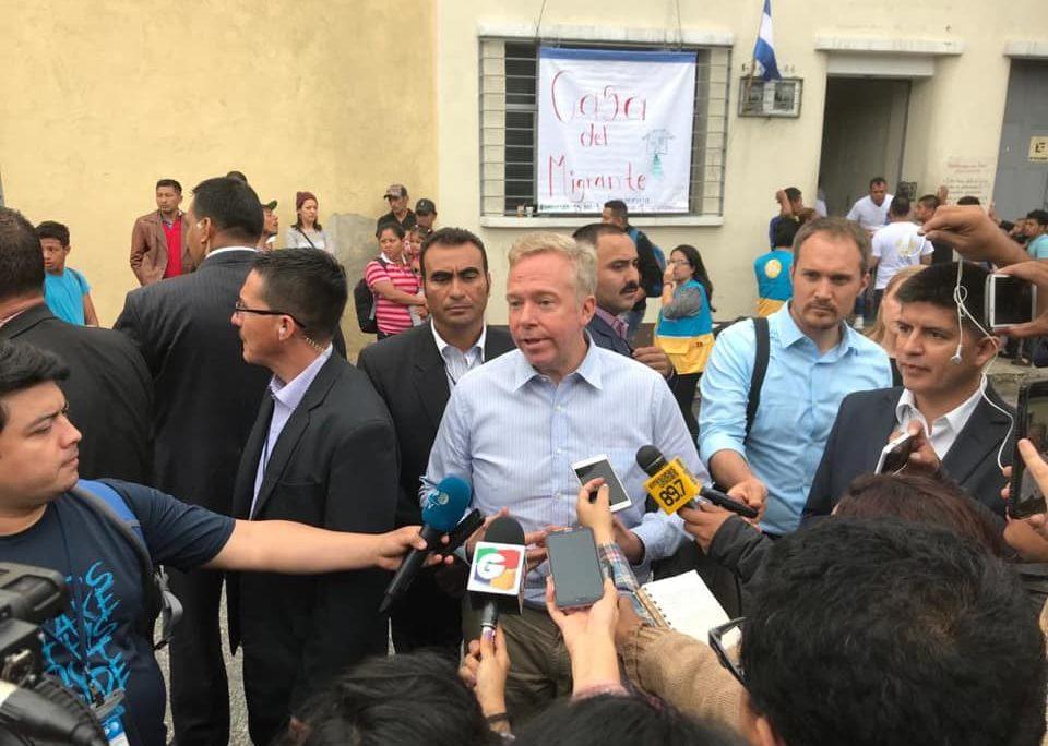 Americano David Hodge em entrevista a jornalistas na Guatemala. Aparece rodeado por repórteres segurando microfones. Veste camisa azul clara.