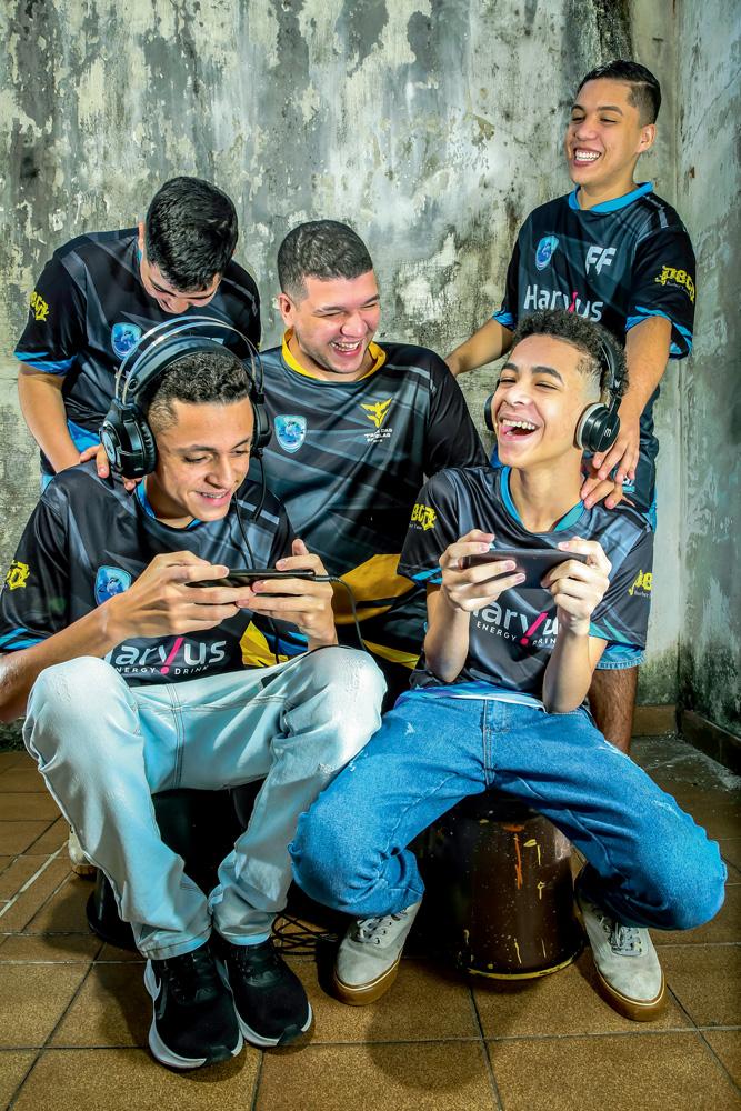 A imagem mostra Cauê, Felipe, Nycolas, Davi e Ryan Barbosa, todos rindo enquanto jogando Free Fire no celular. Todos estão com o uniforme preto da equipe.