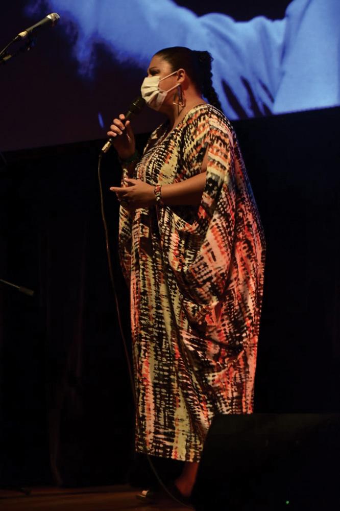 De vestido e máscara, uma mulher canta em um palco de teatro