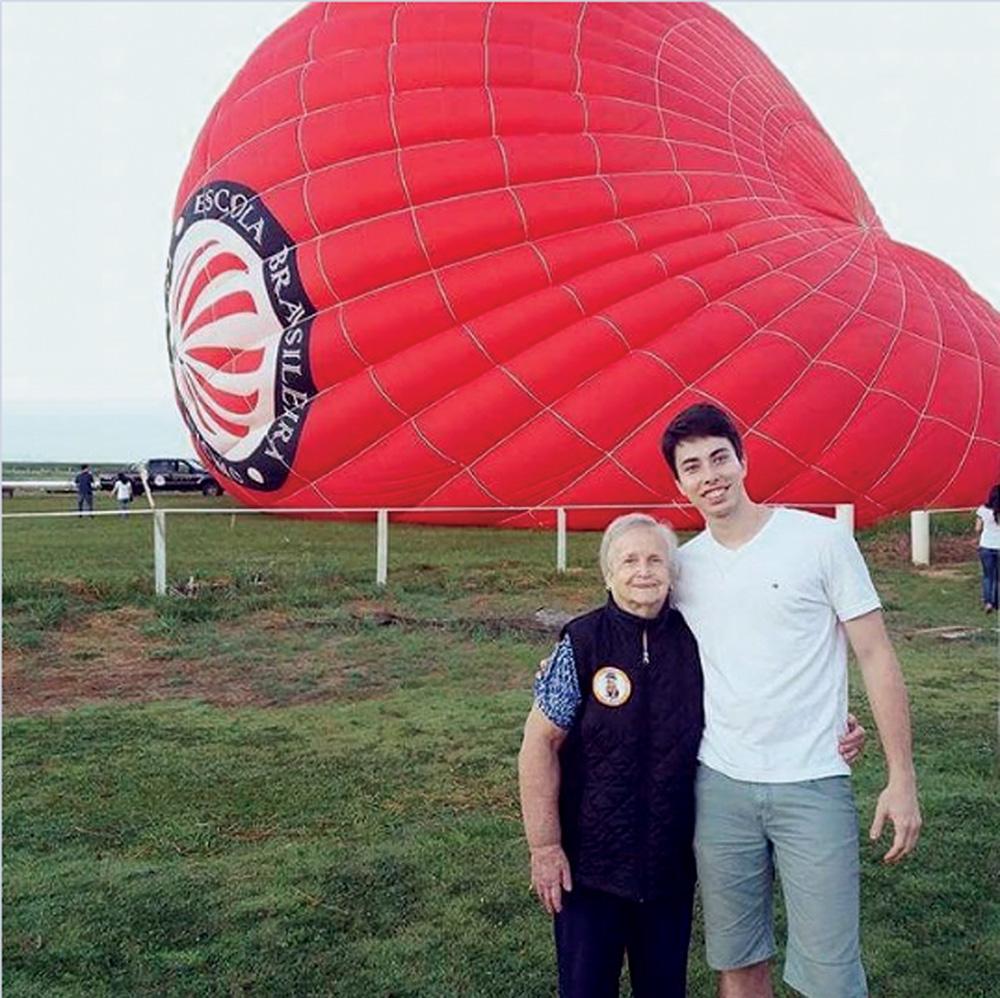 felipe e joanna nascimento posando para a foto em campo em Boituva, com balão vermelho ao fundo