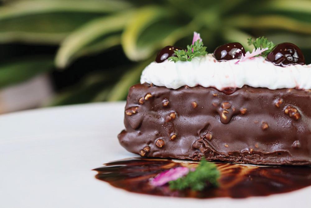 Bolo floresta negra, feito à base de pão de ló, com recheio de brigadeiro com chantili, cereja e puxuri, servido em uma prato raso de cor branca