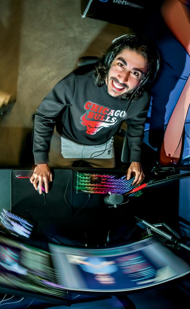 A imagem é uma foto tirada de cima de Baiano. Ele está olhando para cima, sentado em frente ao seu monitor, com um teclado colorido e sorrindo.