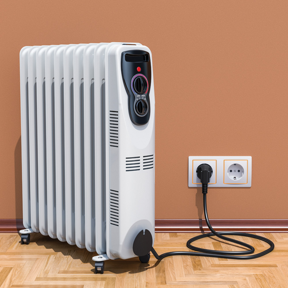 Um aquecedor de tomada está plugado em uma parede laranja com piso de madeira