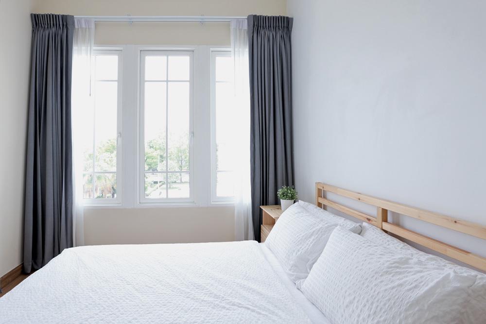 Vista lateral de uma cama de madeira branca moderna em quarto branco com luz suave e clara