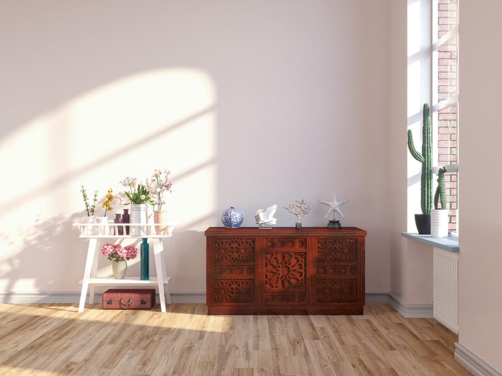 Vista para um cômodo de madeira, uma mini estante com flores e, ao lado, uma janela com bastante luz do sol entrando