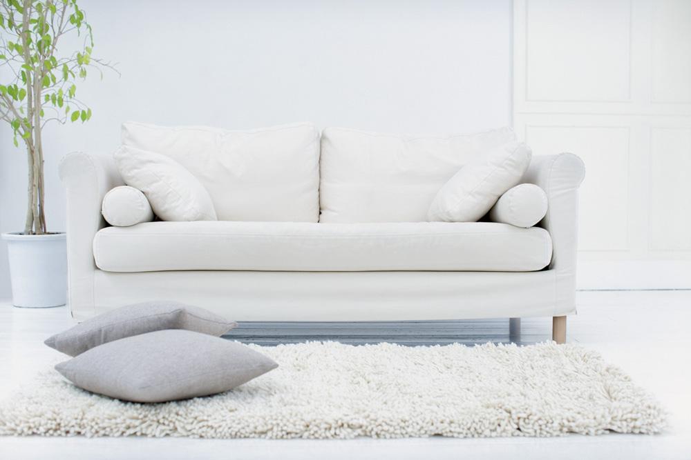 Uma sala de estar com tons de branco. Tem um sofá, duas almofadas no chão e um tapete de pelinhos