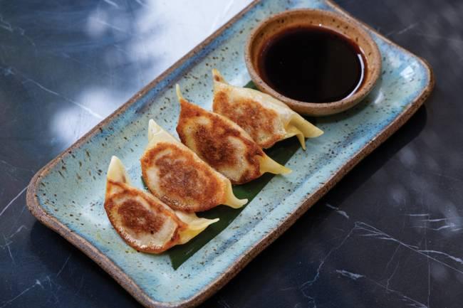 Prato retangular de cerâmica azul com quatro guiozas um ao lado do outro junto de potinho com molho de shoyu.