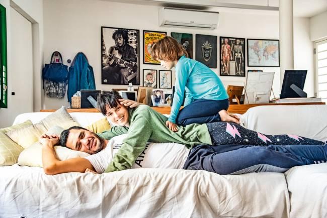 Bruno Kayapy deitado em sofá da sala de casa com a chef Helena Rizzo abraçada sobre ele com a filha Manoela em cima de suas costas.