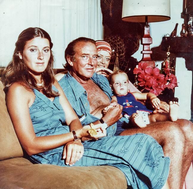 Helena Rizzo bebê no colo da avó paterna ao lado do avô e a mãe, todos sentados num sofá marrom à esquerda.