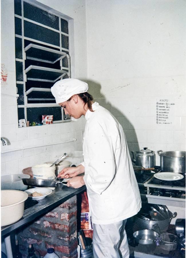 Heleha Rizzo de perfil de dólmã e touca cozinhando no restaurante Puppi Baggio.