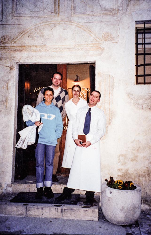 Helena Rizzo de moletom azul no portal do restaurante La Torre, na Itália, ao lado de uma mulher e homem com trajes de serventes e outro homem postado logo atrás dela.