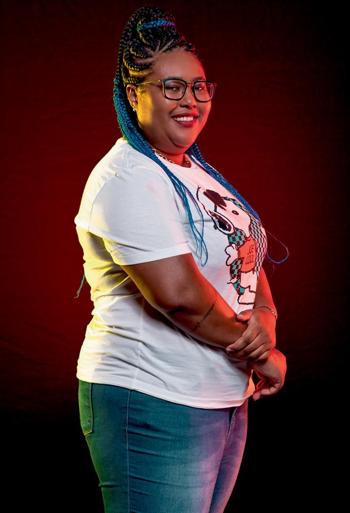 A imagem mostra Maah, em um fundo vermelho, sorrindo para a foto