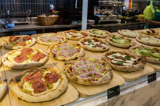 Pizzas individuais em vitrine sobre assadeiras de madeira.
