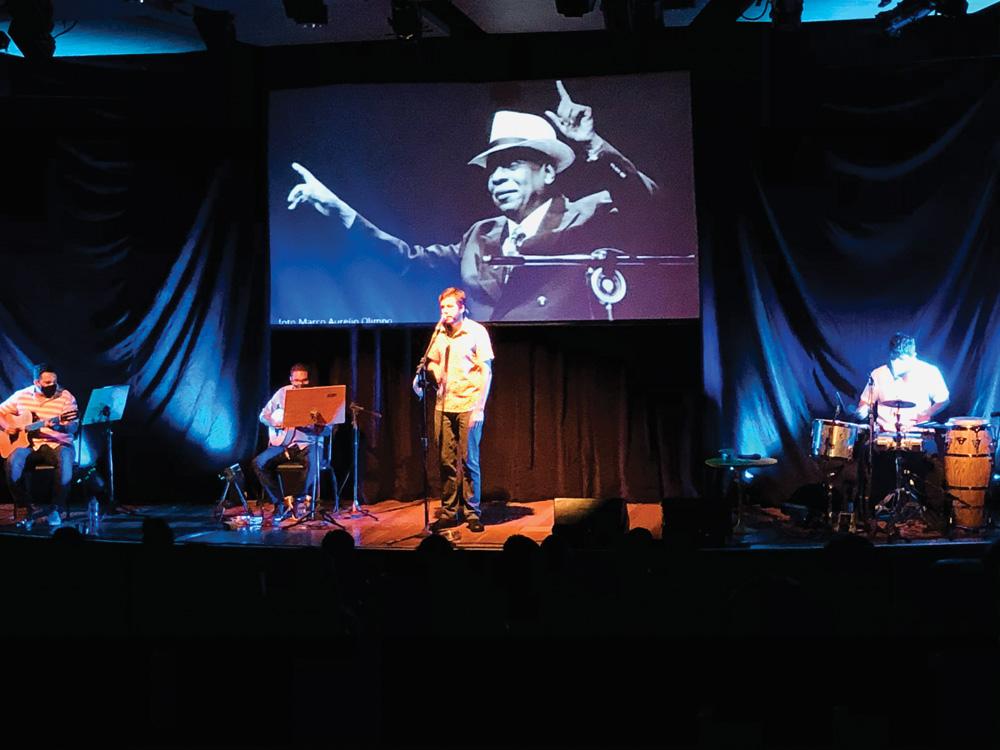 Em um palco, um homem canta com microfone, outros dois tocam violão e bateria e, ao fundo, um telão passa uma foto do cantor Zé Kéti