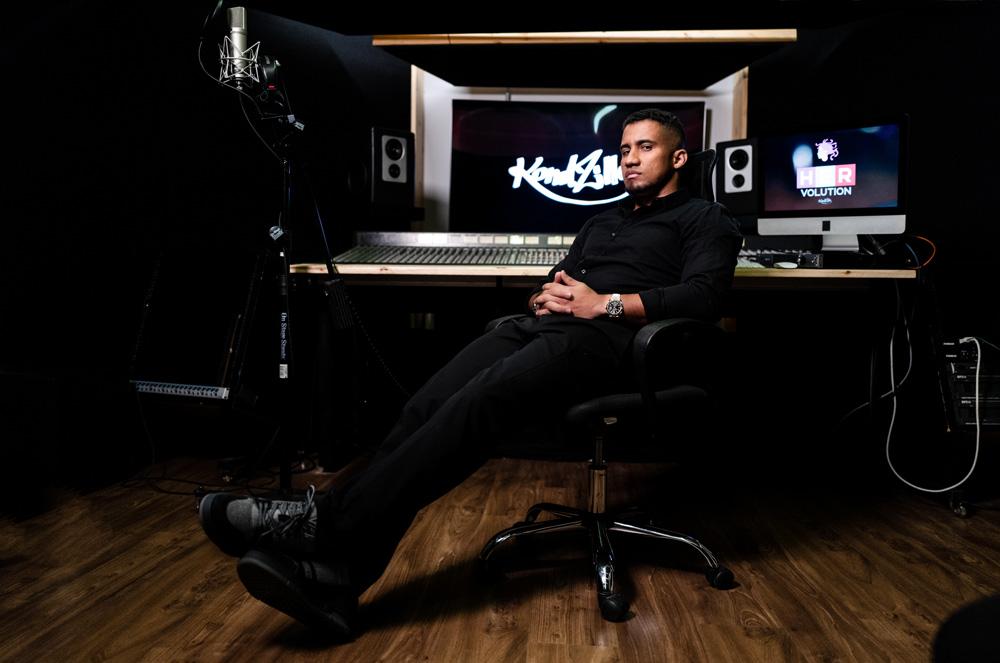 A imagem mostra Konrad, sentado em uma cadeira dentro de um estúdio. Há, ao fundo, um enorme mesa de mixagem de som e um telão ao fundo escrito KondZilla.