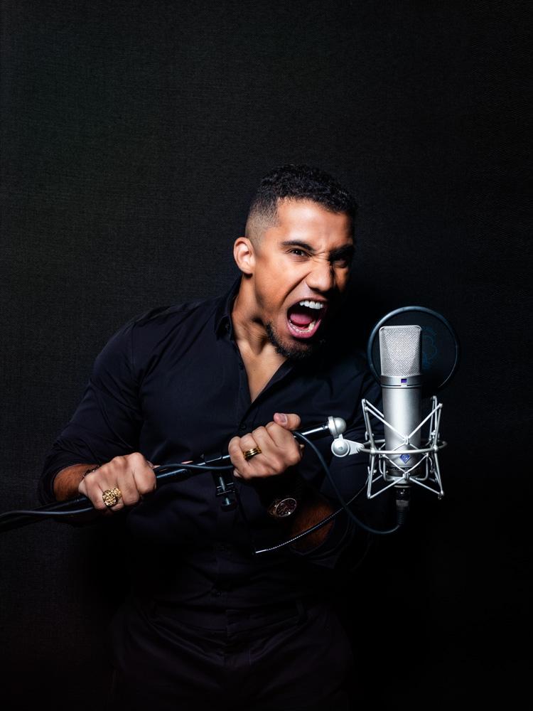 A imagem mostra Konrad segurando um microfone e gritando.