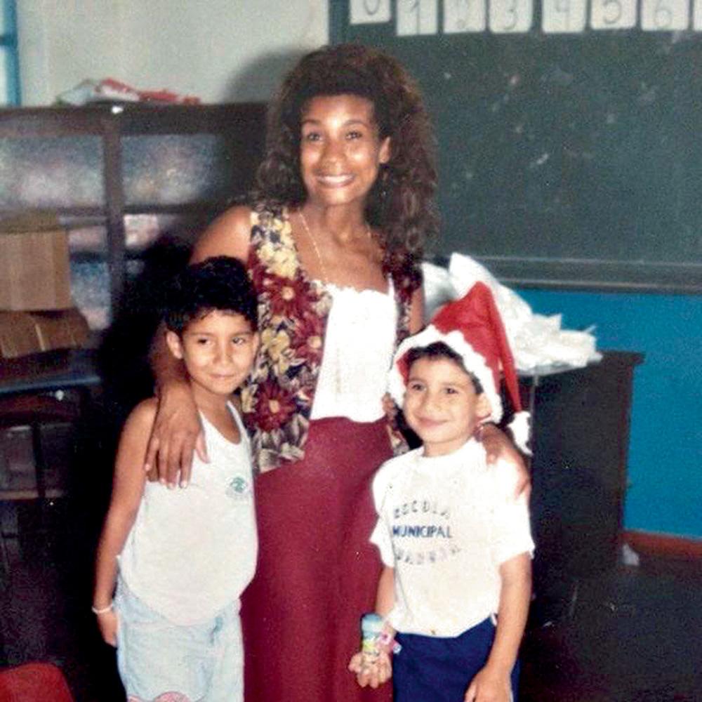 A imagem mostra a mãe de Konrad, Áurea Cunha, com mão nos ombros de duas crianças, com os três sorrindo para a câmera. Ao fundo, há uma lousa verde mostrando que eles estão em uma sala de aula.