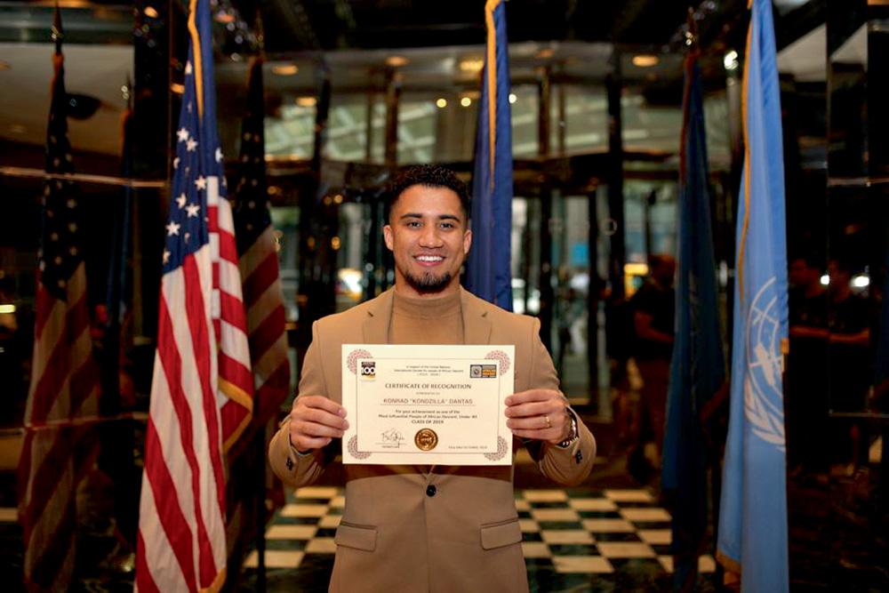 A imagem mostra Konrad segurando o certificado e ao fundo há as bandeiras dos Estados Unidos e ONU.