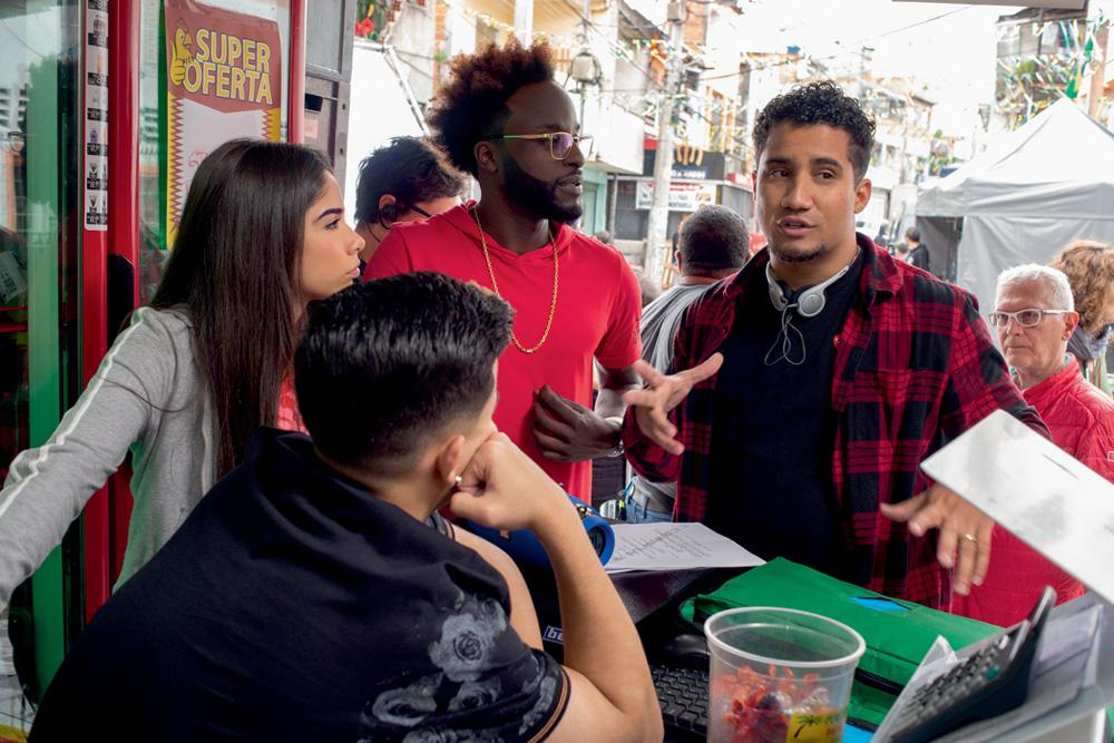 A imagem mostra Konrad conversando com três atores da série Sintonia.