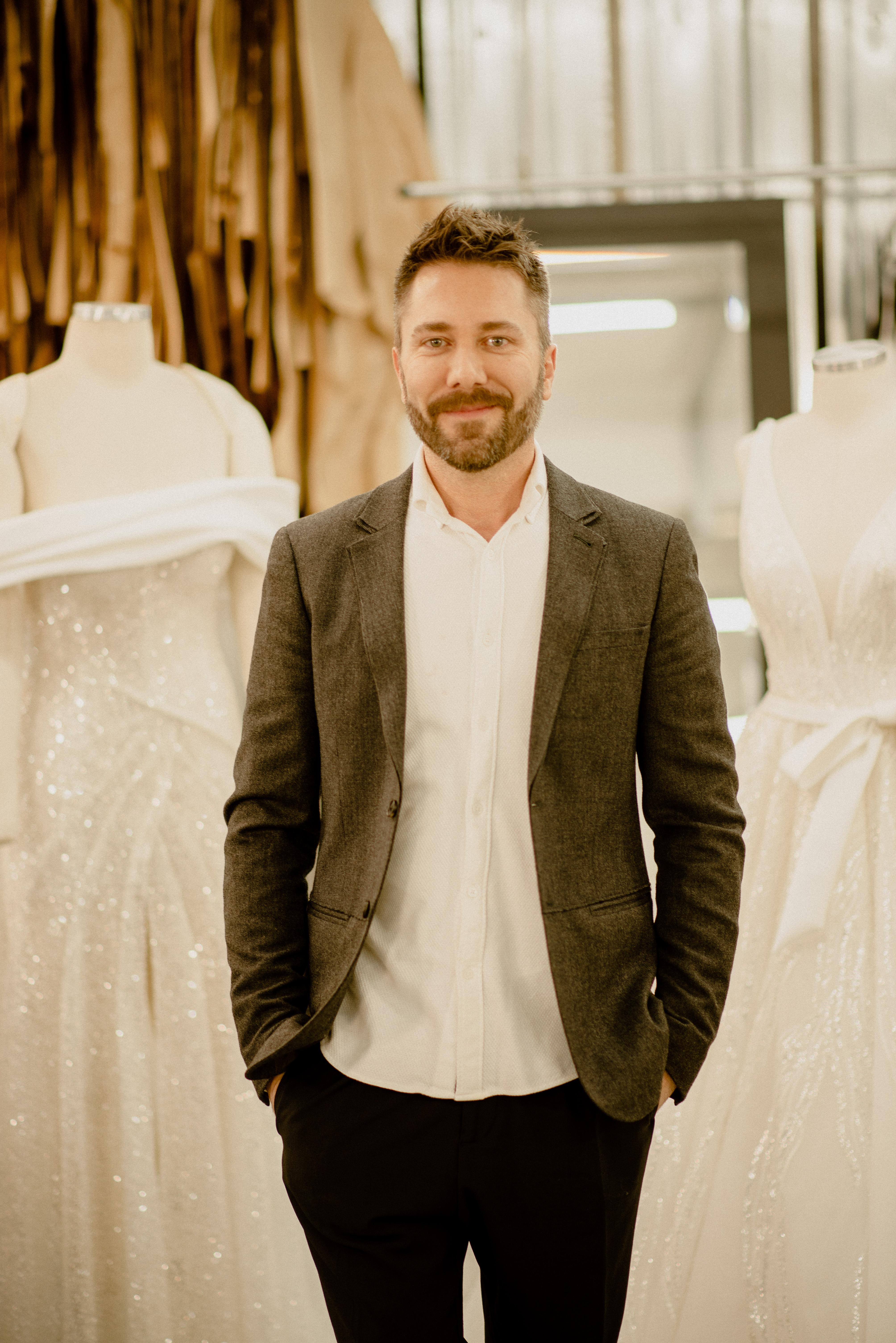 Lucas Anderi posa com as mãos no bolso vestindo paletó escuro e camisa branca. Dois vestidos de noiva aparecem de fundo.