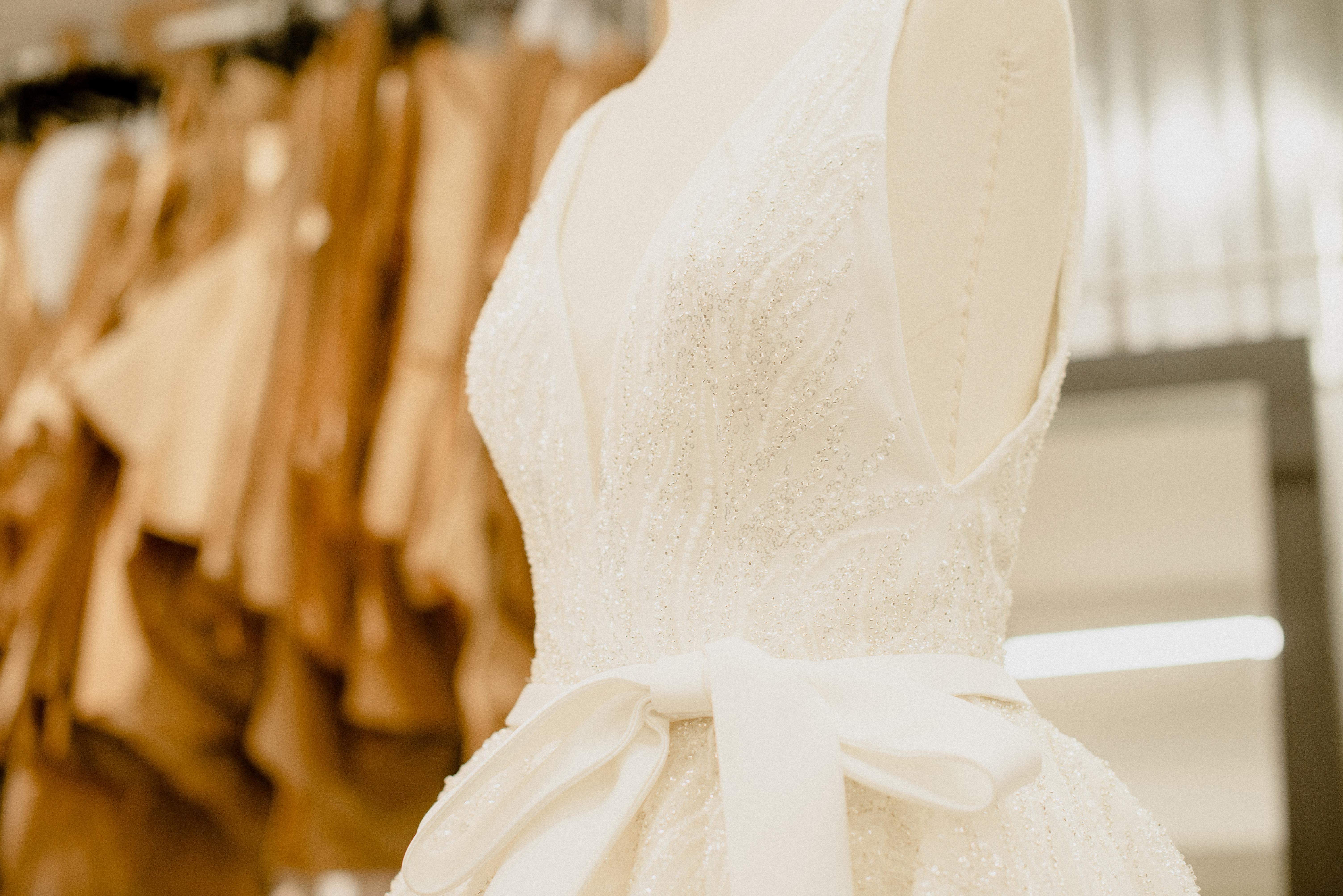Imagem exibe parte de vestido de noiva branco com laço na altura da cintura.