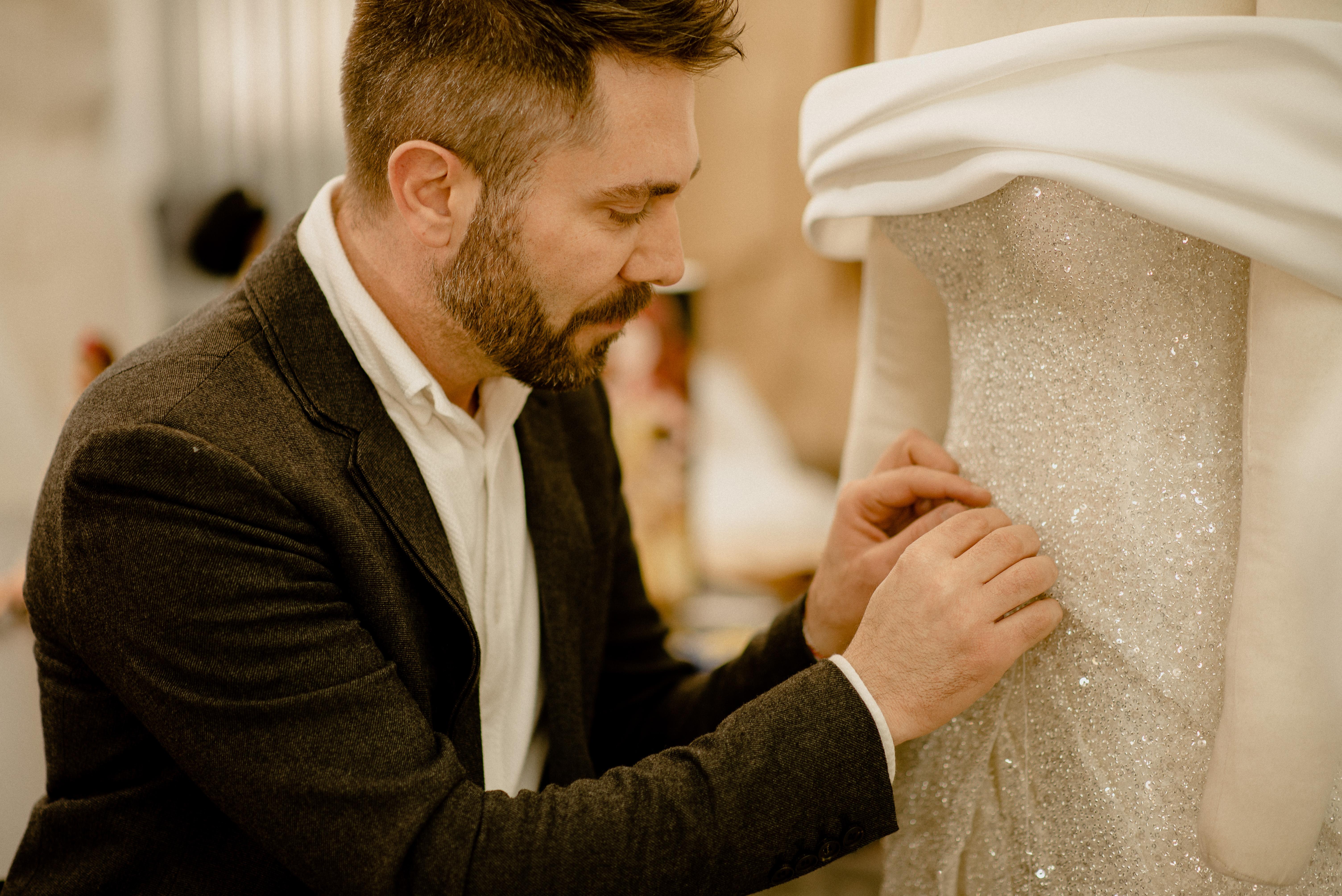 Lucas Anderi costura trecho de vestido de noiva na imagem. Aparece de paletó preto e camisa branca.