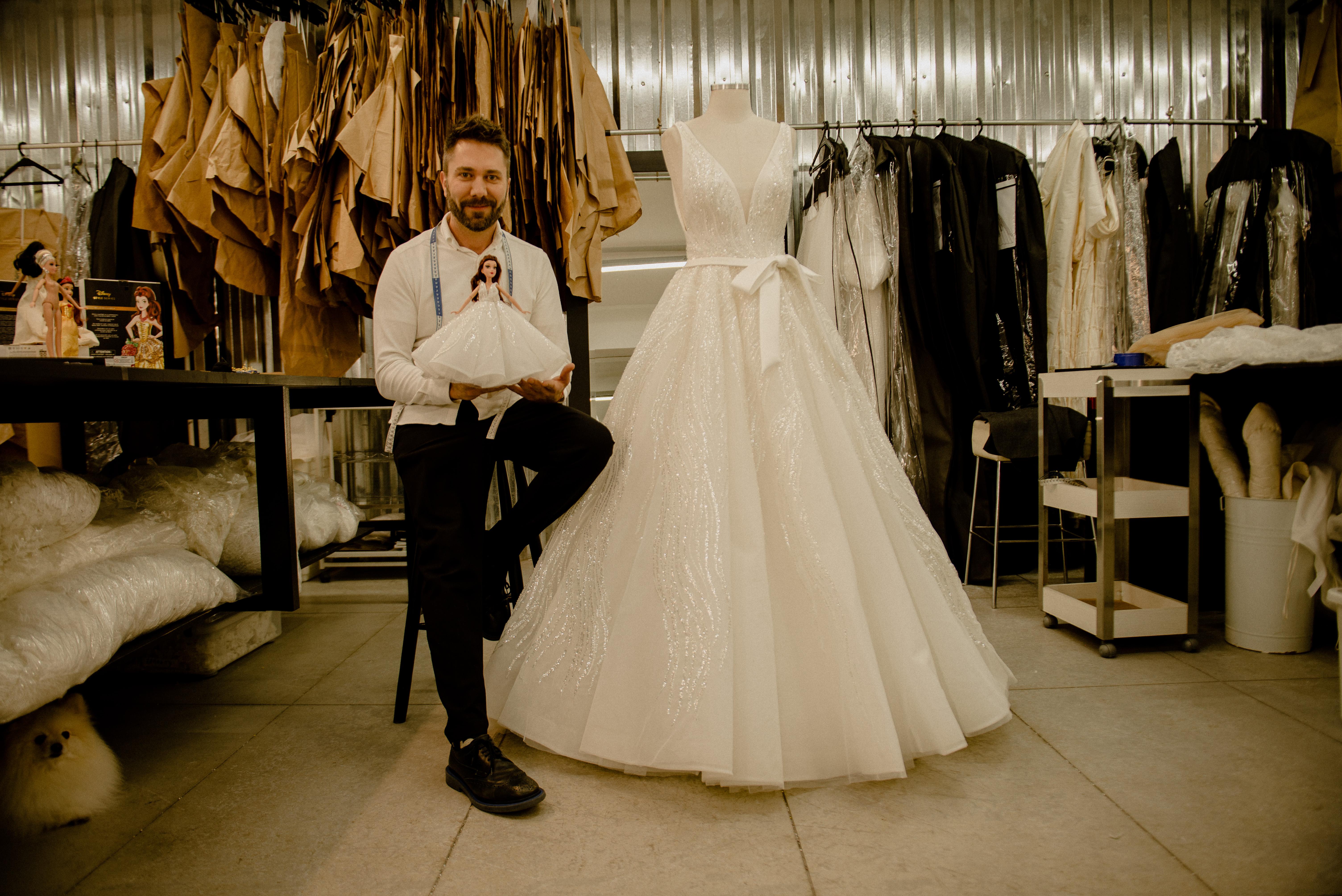 Lucas Anderi aparece sentado ao lado de vestido de noiva. Veste calça preta e camisa branca, com fita métrica no pescoço e segurando boneca.
